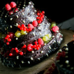 chocolate wedding cake with berries on wood disk