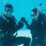 Man proposing marriage to his shocked girlfriend underwater in s
